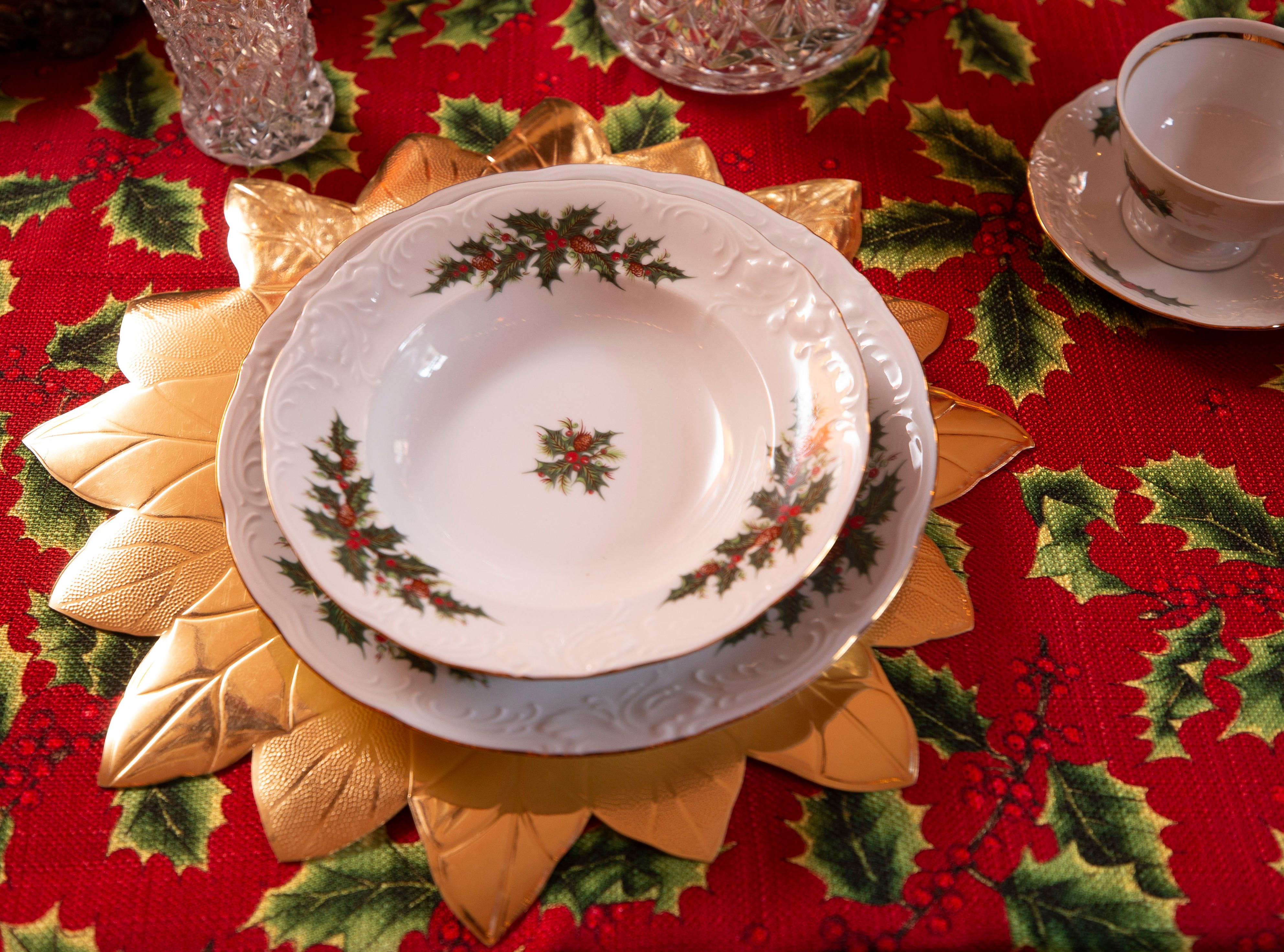 A placesetting in the Kitchen has the holiday theme, from the tablecloth to the china with the holly motif.