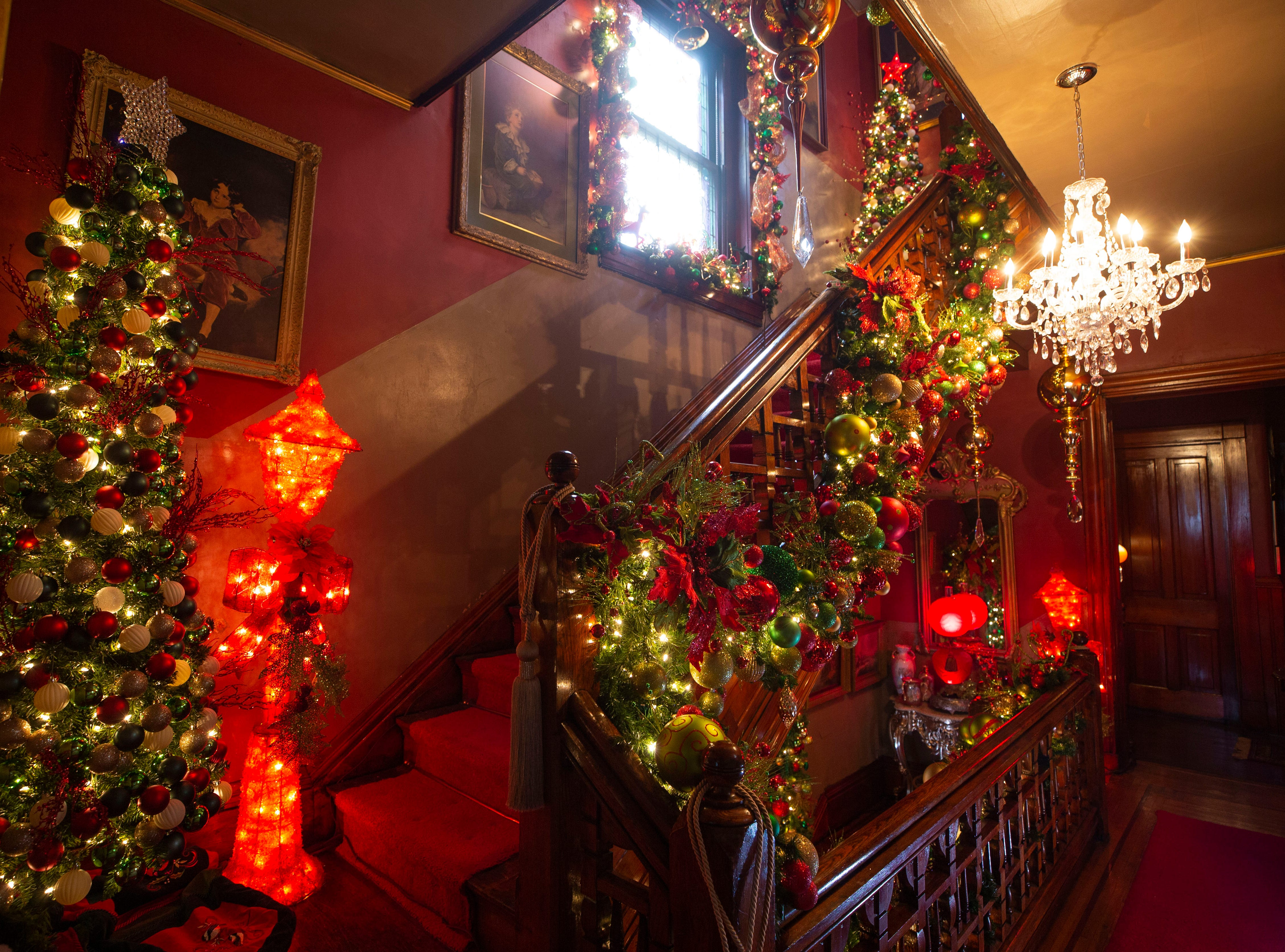 A three story staircase with over 7,000 ornaments displayed in garland.
