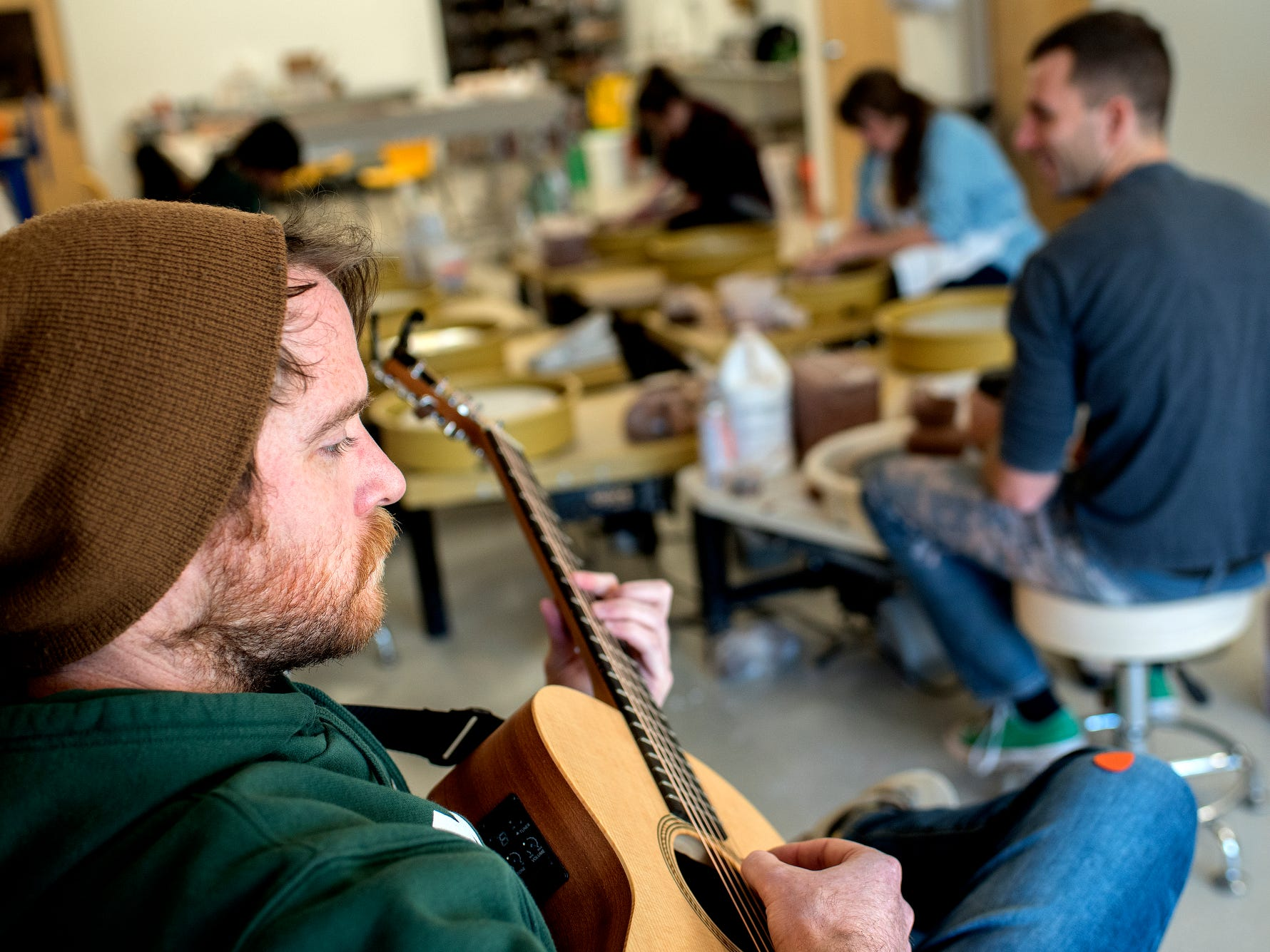 Mike McConeghy plays music at his friend Dan Nunez's business the Wheel House Studio on Wednesday, Nov. 14, 2018, in Lansing.