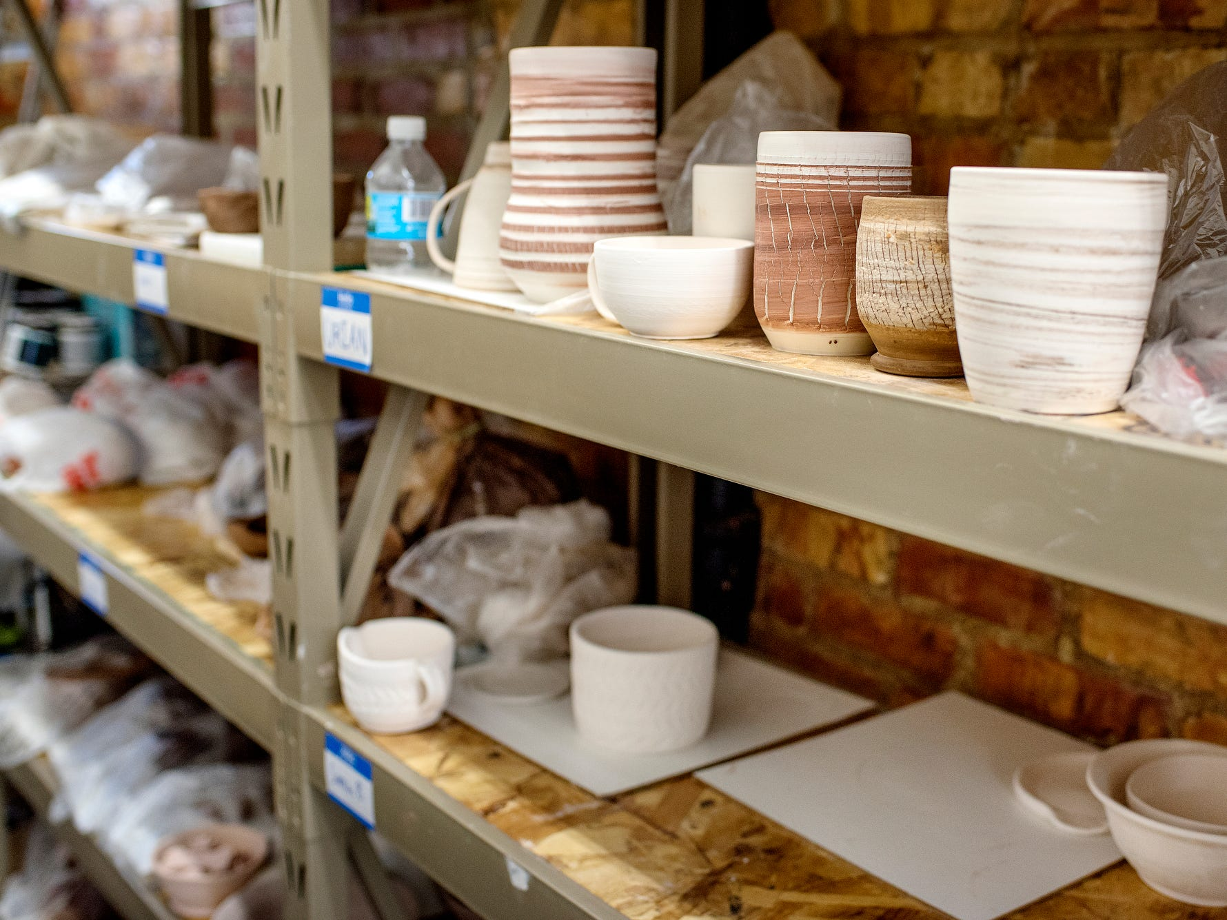 Shelves hold pieces that students are working on at the Wheel House Studio on Wednesday, Nov. 14, 2018, in Lansing.