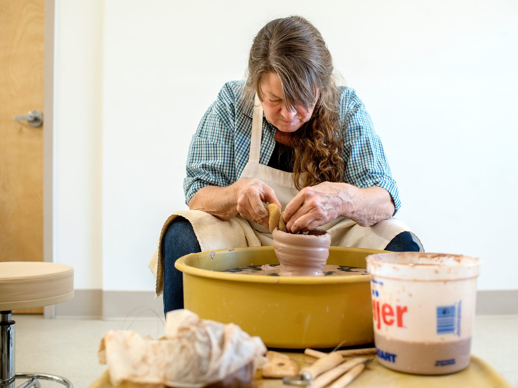 Carole Schmidt works on a pot during a class at the Wheel House Studio on Wednesday, Nov. 14, 2018, in Lansing.