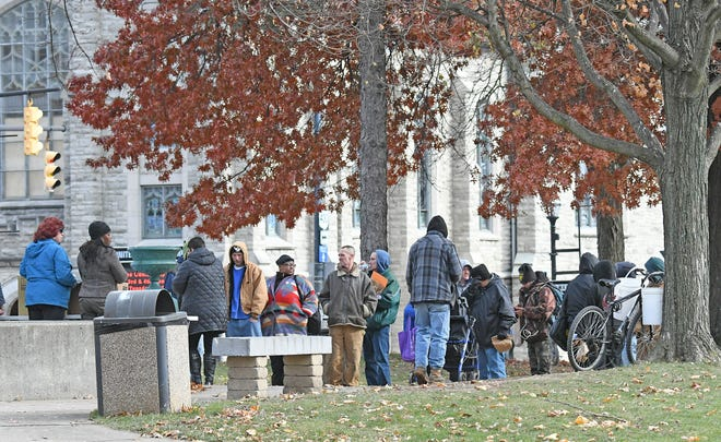 Hungry people from the area line up for free food in downtown Mansfield one day earlier this month. Food is served at 11 a.m. daily in Central Park. to all in need of a meal.