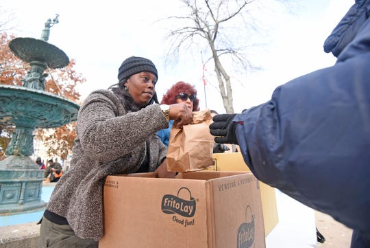 Latonda Williams and Sharon Subich, both from Liberty Nursing Home, feed the hungry on Nov. 14 in downtown Mansfield.