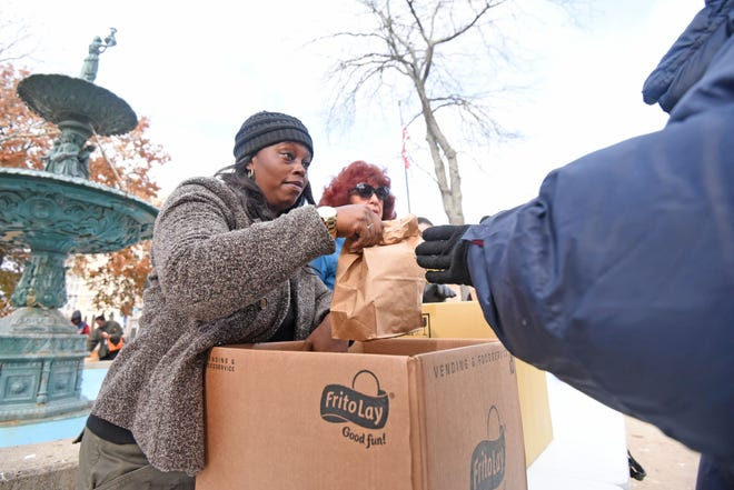 Latonda Williams and Sharon Subich, both from Liberty Nursing Center, feed the hungry on Nov. 14 in downtown Mansfield.