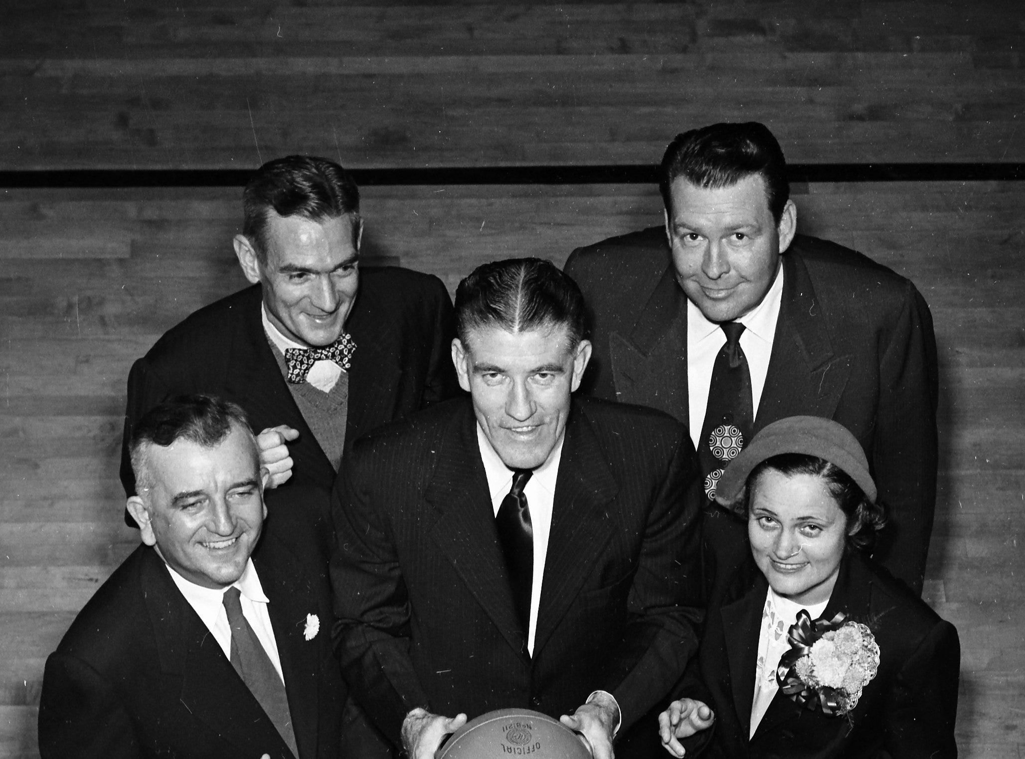 George H. Barnes (Center), superintendent of Shelby County Schools, eyes the hoop for a shot at the dedication of the new gym and auditorium at Frayser High School in November 1951.  Pulling for Mr. Barnes were Ira Knox (Left), Fraser Boosters representative, L. M. Stevenson (Second Left), Frayser High principal, Dr. Bascom Story (Second Right), Memphis State faculty member and featured speaker and Mrs. Carl Powers (Right), president of the Frayser P.T.A.