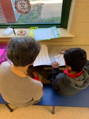 "A volunteer works with a second grader to help him become a proficient reader. The volunteer is part of ""Team Read."""