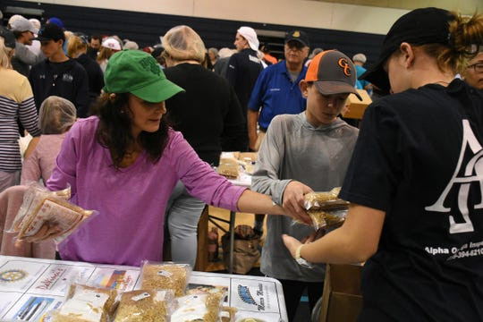 Volunteer Wendy Sweeney stacks completed bags of food. Marco Island volunteers packed a quarter of a million meals to feed those in need of food at the Meals of Hope packaging event Saturday morning at Marco Island Charter Middle School.