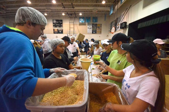 Wesley Hertgers, 16, and Nicole Politi, 15, work to fill bags of meals. Marco Island volunteers packed a quarter of a million meals to feed those in need of food at the Meals of Hope packaging event Saturday morning at Marco Island Charter Middle School.