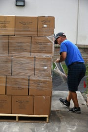 Driver Fred Smith plastic wraps a pallet-load of boxes for transport. Marco Island volunteers packed a quarter of a million meals to feed those in need of food at the Meals of Hope packaging event Saturday morning at Marco Island Charter Middle School.