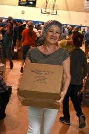 A volunteer brings a filled box to the waiting pallets. Marco Island volunteers packed a quarter of a million meals to feed those in need of food at the Meals of Hope packaging event Saturday morning at Marco Island Charter Middle School.