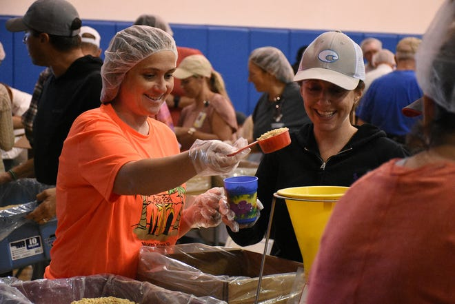 Cub Scout leaders Brandi Garwood, left, and Renee Reed fill bags with their team. Marco Island volunteers packed a quarter of a million meals to feed those in need of food at the Meals of Hope packaging event Saturday morning at Marco Island Charter Middle School.