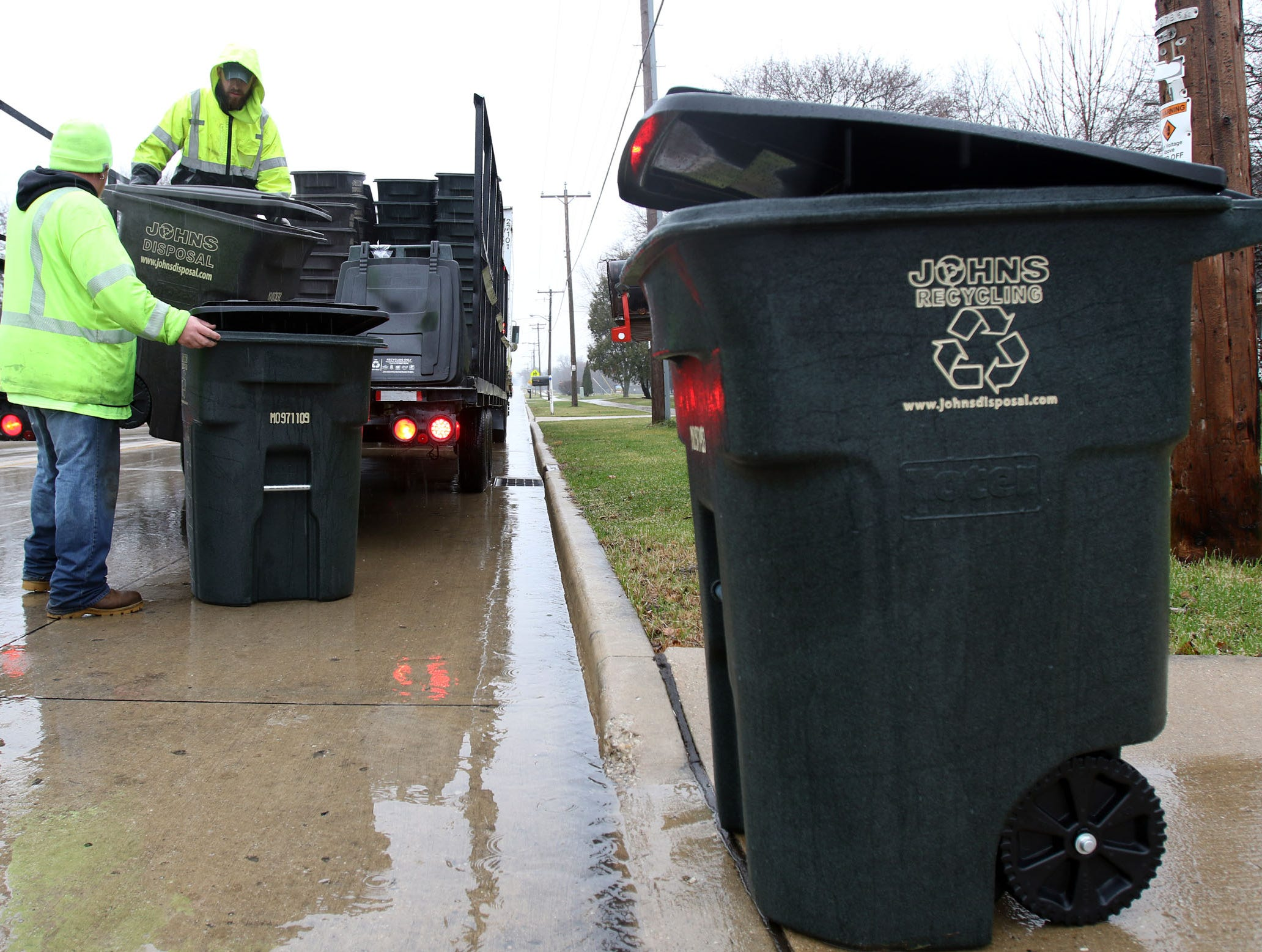 Steve Lyman, left, and Nate Austin distribute new garbage and recycling carts to residents along Maple Avenue in Sussex in December 2015.