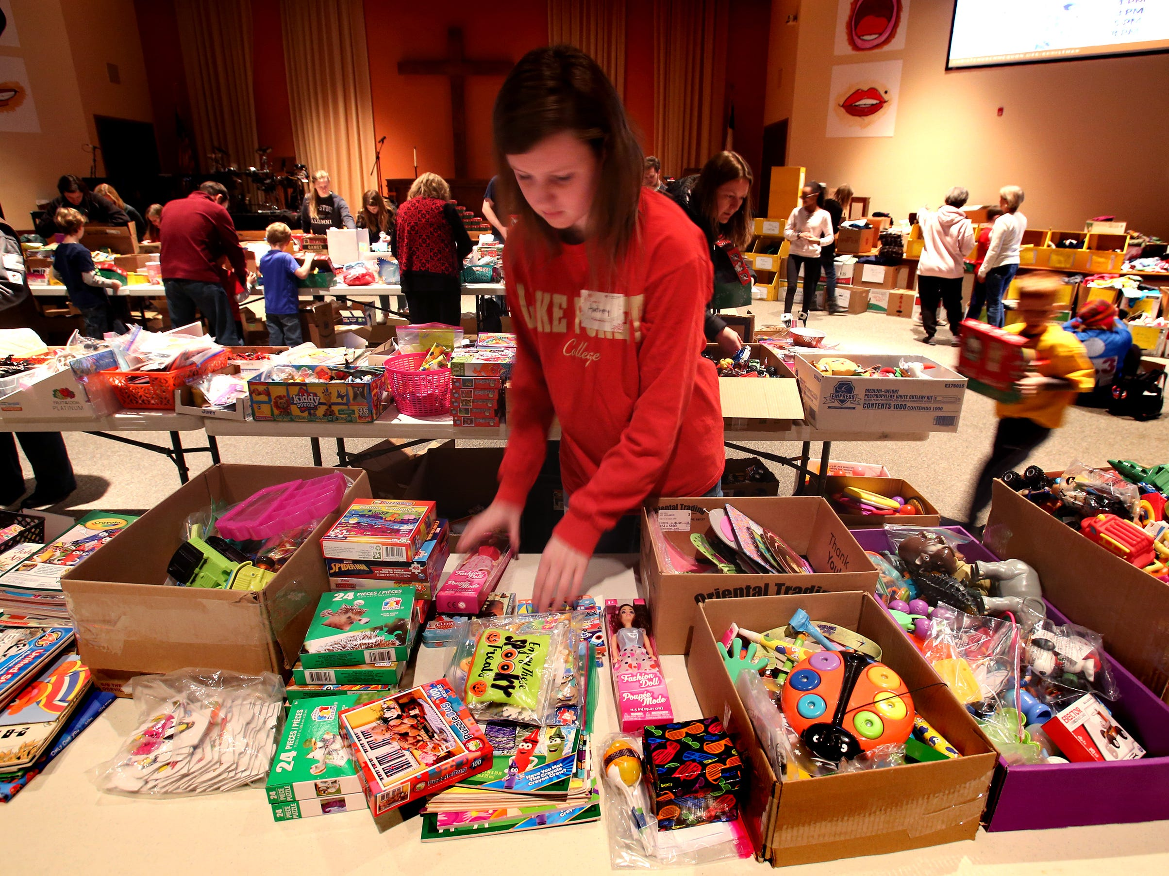 Audrey Lane puts out items to be selected by volunteers to fill shoebox-sized containers for the worldwide Operation Christmas Child at Mequon's Christ Church on Nov. 17.
