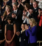 First lady Michelle Obama is applauded before President Barack Obama's State of the Union address in Washington on Feb. 12, 2013. Front row, from left are:  Obama, Menchu de Luna Sanchez and Jill Biden. Second row, from left are: New Glarus Brewing Co. co-founder Deb Carey, Apple CEO Tim Cook, Amanda McMillian and Oak Creek Police Lt. Brian Murphy.