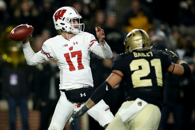 Badgers quarterback Jack Coan  throws a pass while being chased by Purdue's Markus Bailey during their game Saturday.