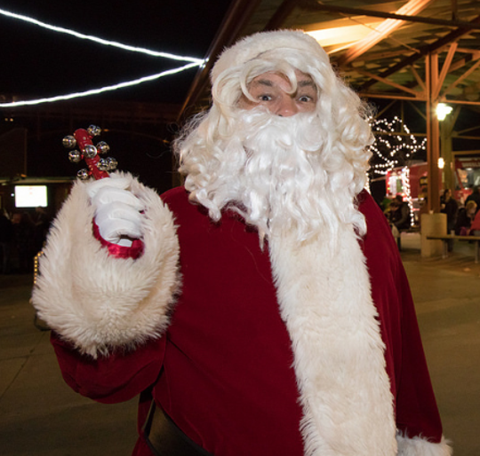 Amid the lights and merriment of the first Christkindl Market, Santa Claus rings those Christmas bells.