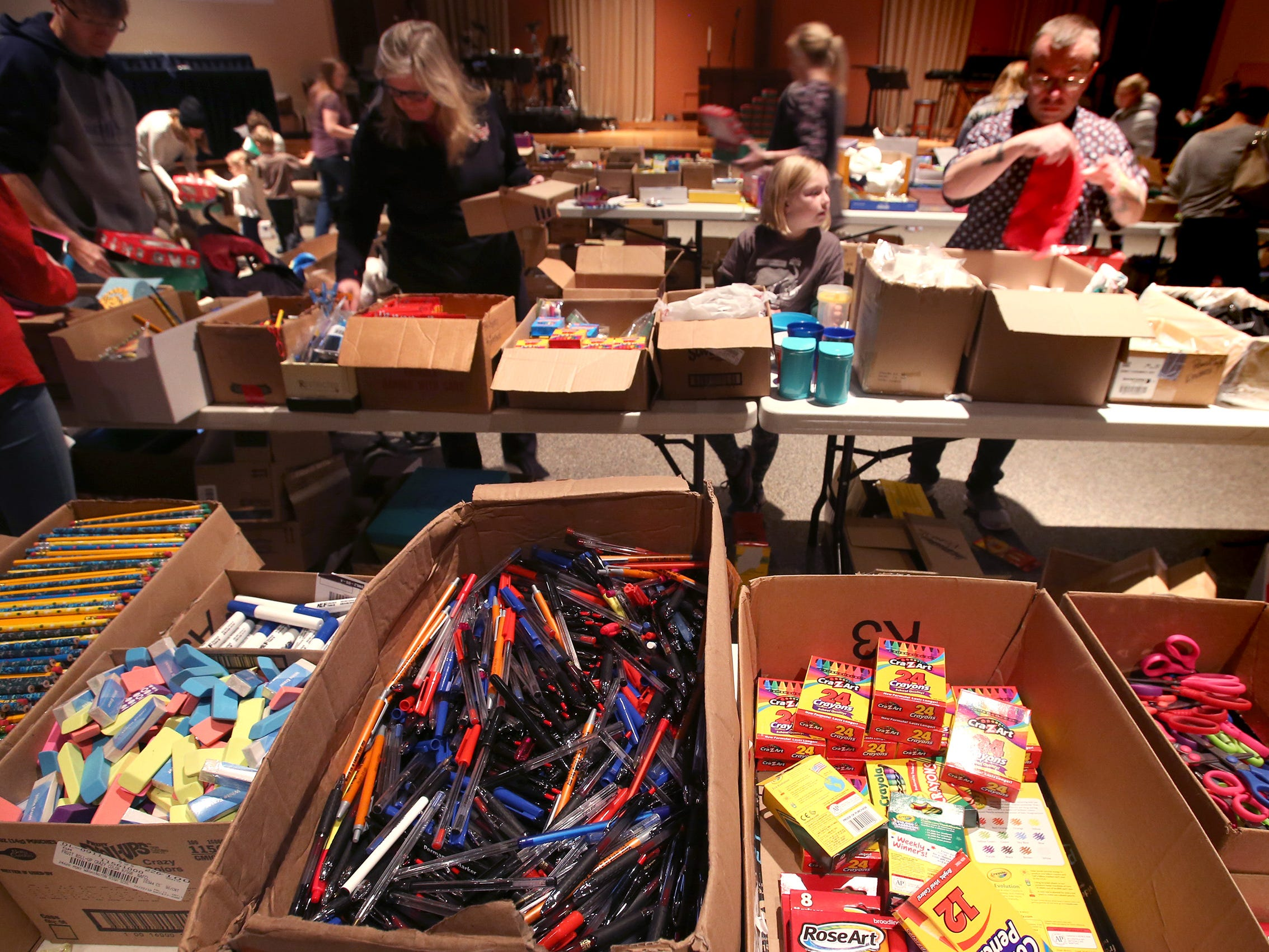 Volunteers select from boxes of school supplies, toys, clothing, personal care items and more to fill shoebox-sized containers for the worldwide Operation Christmas Child at Mequon's Christ Church on Nov. 17.