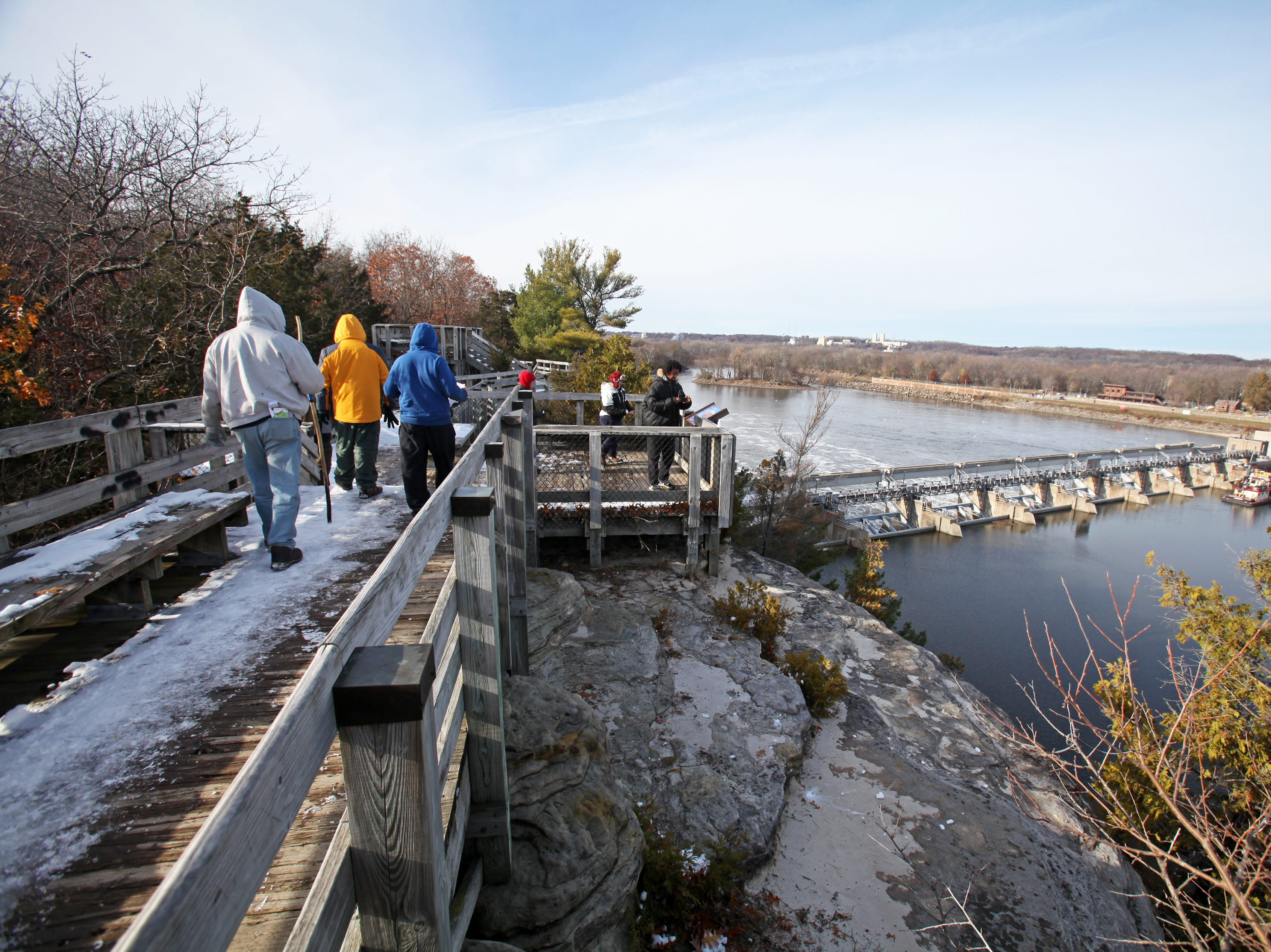 Hikers take in a view of a lock and dam along the Illinois River from the Eagle Cliff Overlook in Starved Rock State Park near Utica, Illinois.