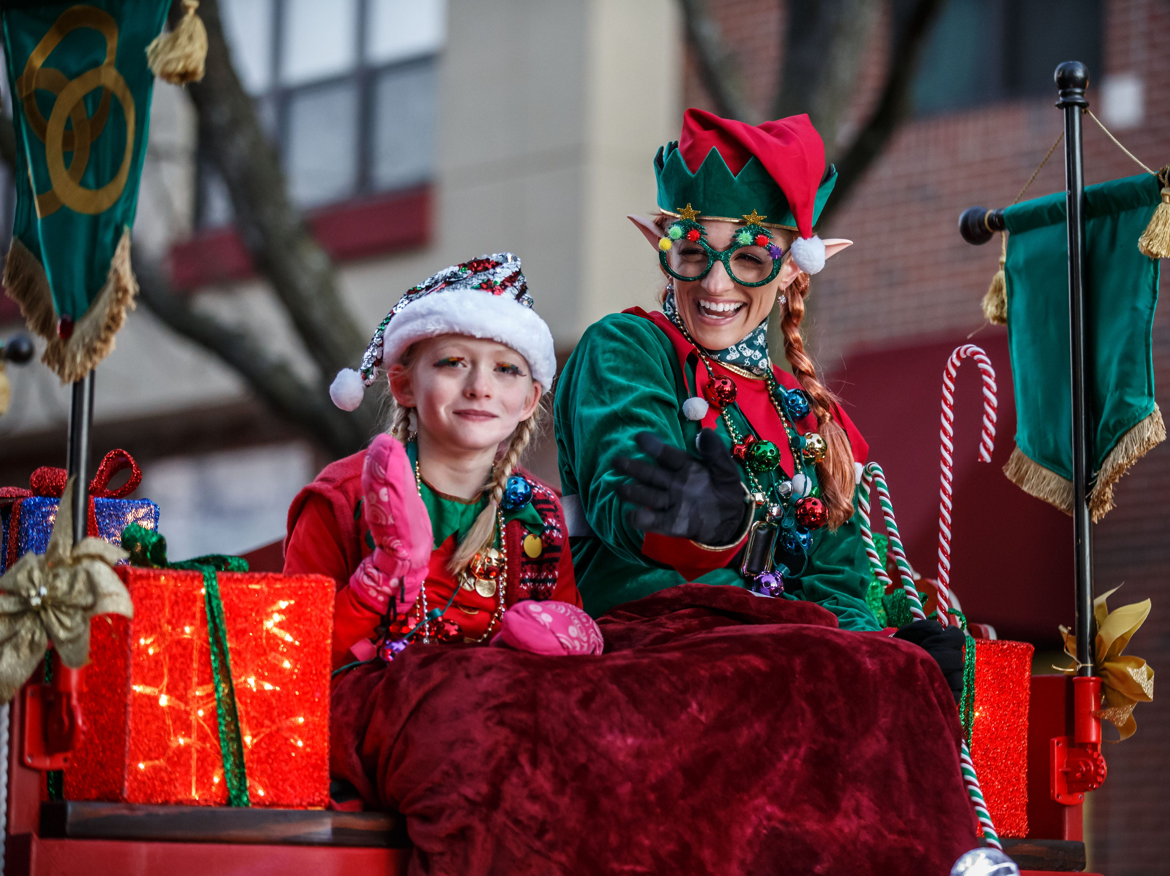 Santa's Elves wave from atop the Whistles on Wheels float during the annual Waukesha Christmas Parade on Sunday, Nov. 18, 2018.