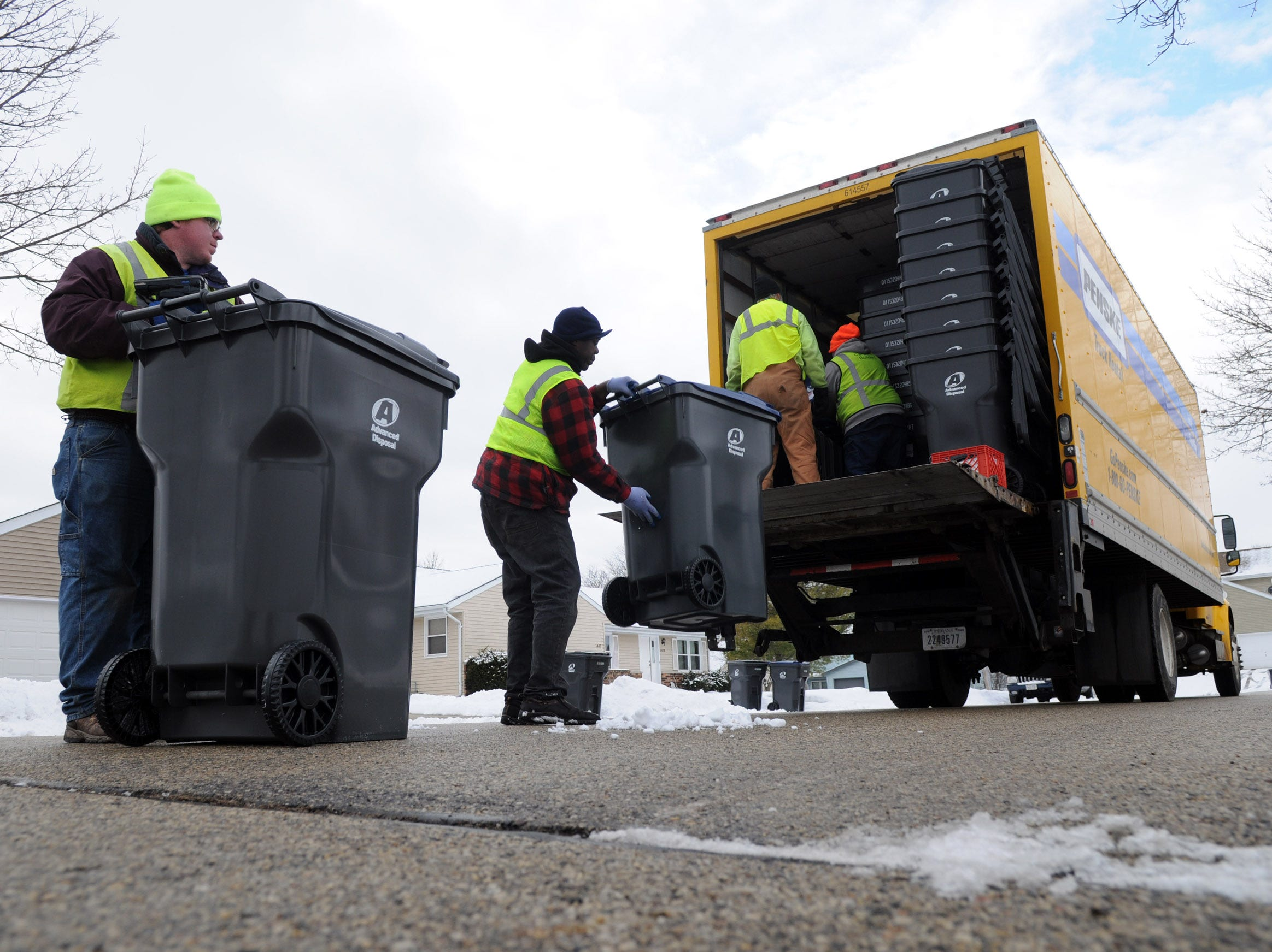 Advanced Disposal crews unload a truck with garbage and recycling bins on American Avenue in Waukesha in January 2015.