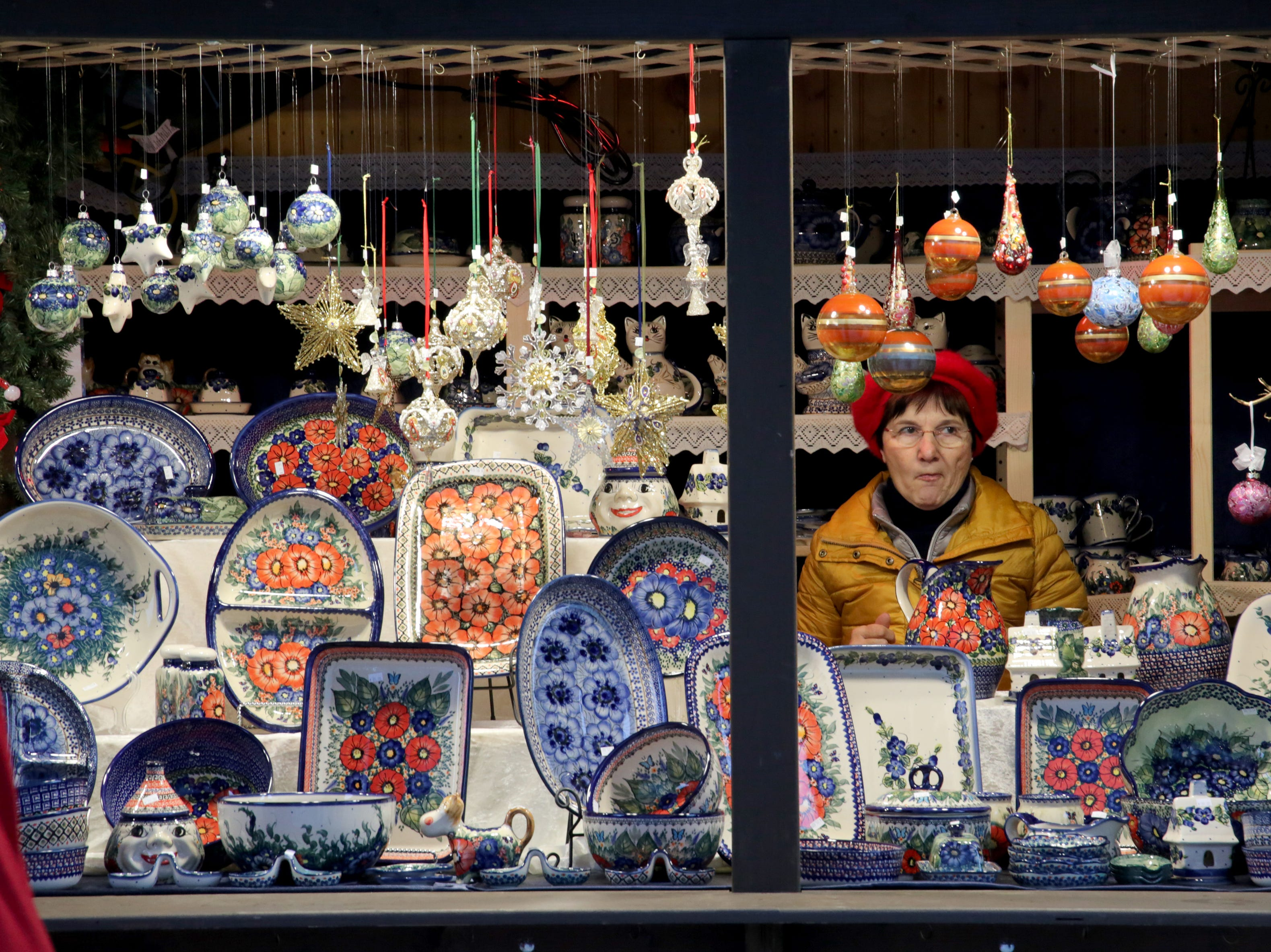 A vendor sits among the various items for sale in her booth. Visitors got a chance to visit the Christkindlmarket German holiday market for its opening weekend.