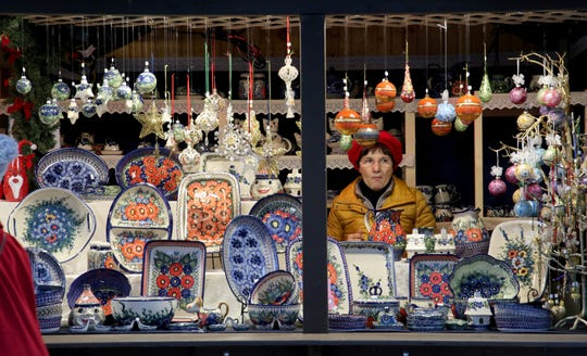 A vendor sits among the various items for sale in her booth at the Christkindlmarket.