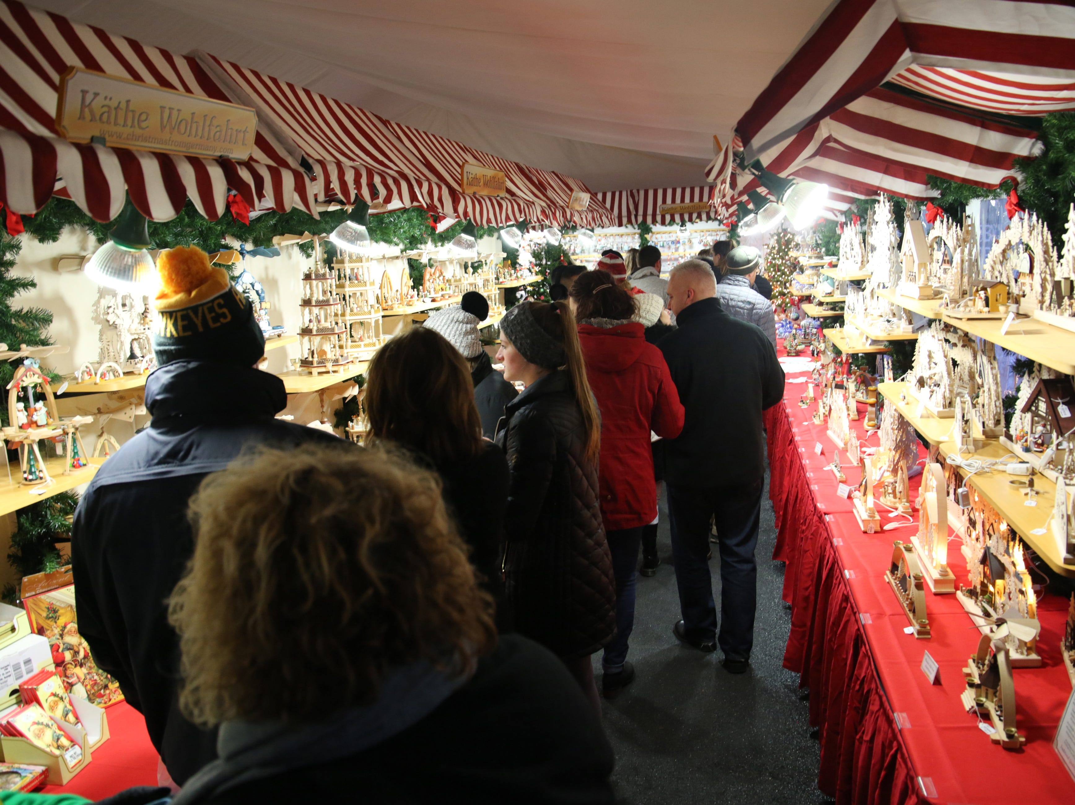 People crowd the Kathe Wohlfahrt tent containing numerous holiday items and ornaments.