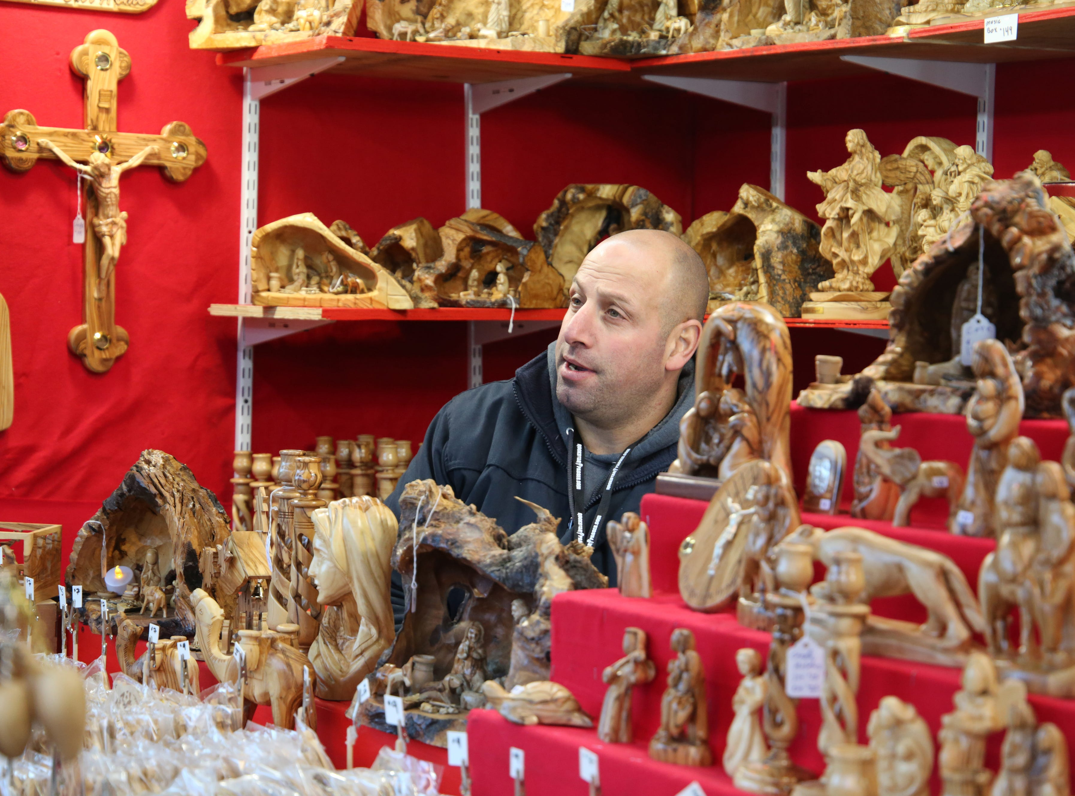 Elias Hosh, with Bethlehem Nativity Products, talks to a customer in the booth that sells carved wooden religious nativities and displays.