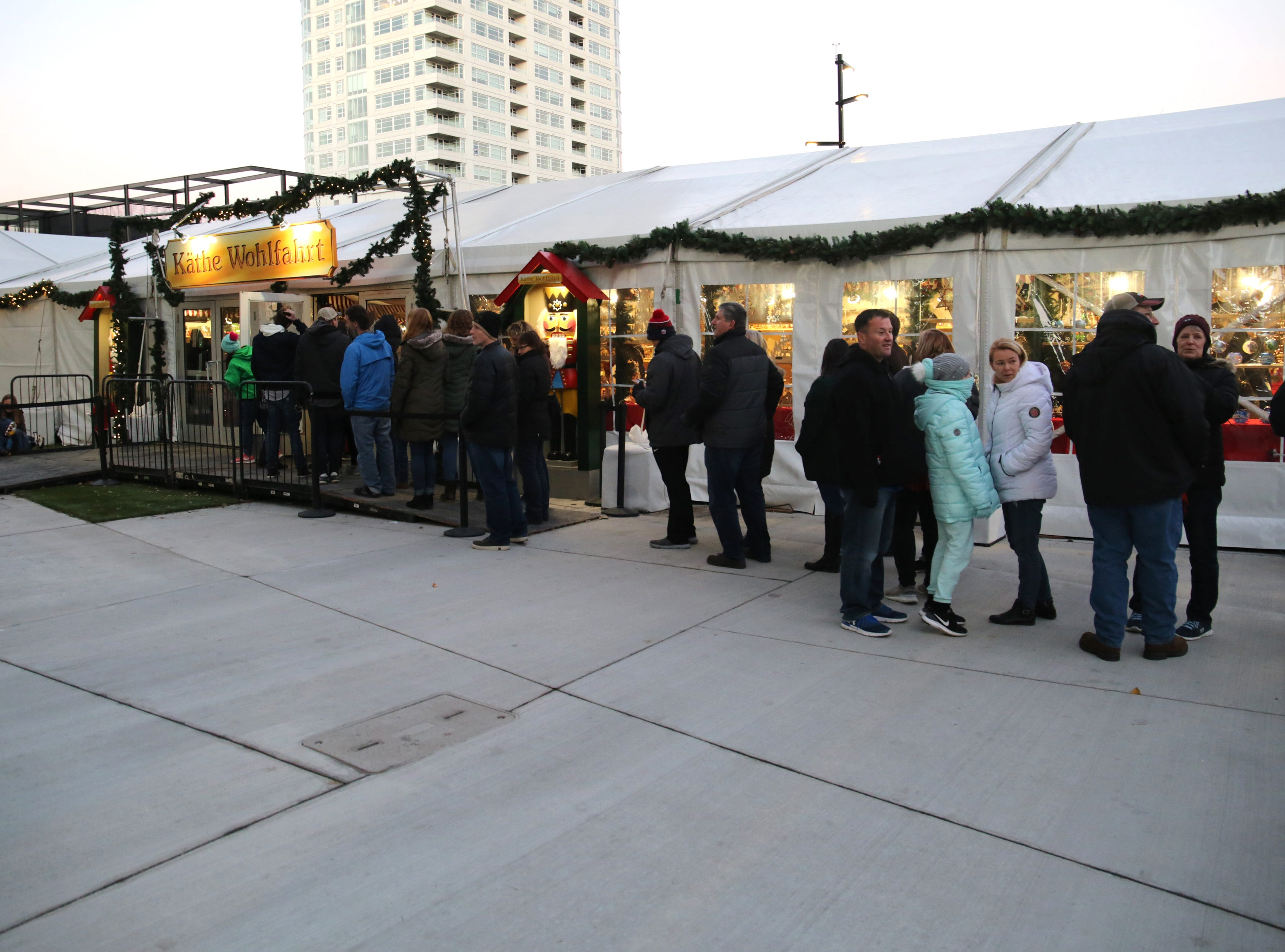 A line of people wait to get into the Kathe Wohlfahrt tent containing numerous holiday items and ornaments.