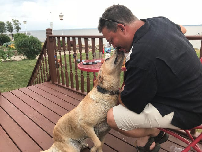 Paul Muche of Van Dyne, Wisconsin, gets a kiss from Jesse, his Labrador retriever.