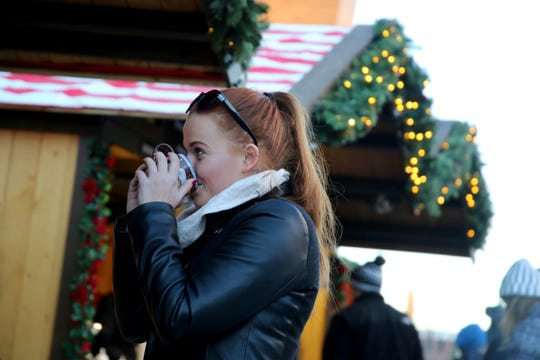 Klara Smolikova, a Cardinal Stritch student from Czech Republic, sips Glühwein, a German wine served warm, at the 2018 Christkindlmarket outside Milwaukee's Fiserv Forum. This year's event continues through Dec. 24.