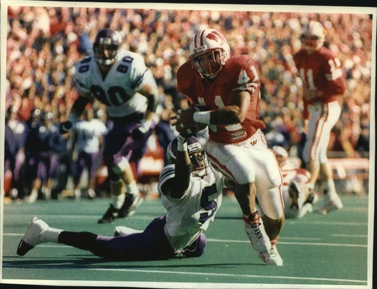 Terrell Fletcher breaks from the grasp of Northwestern's Dwight Brown to score one of his three touchdowns in a 1993 game.