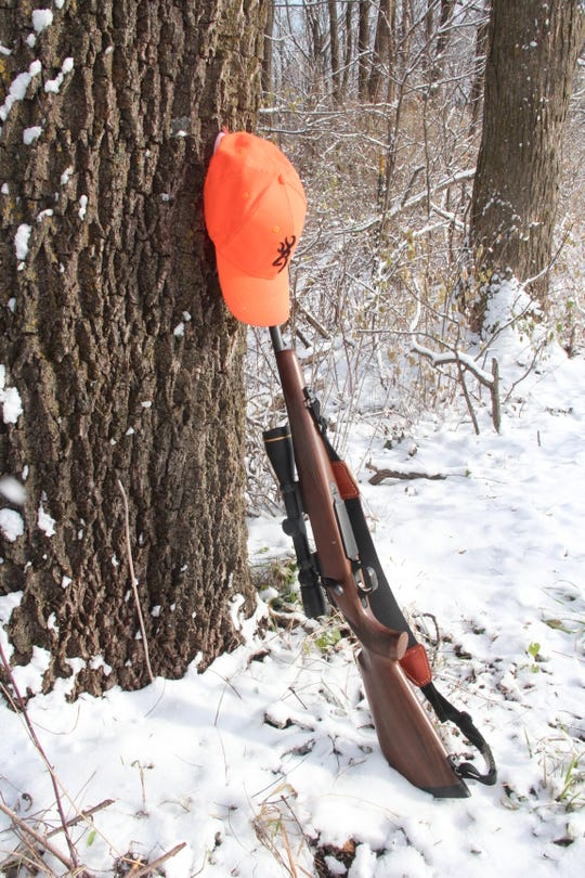 A hunter's rifle and blaze orange cap rest on a tree near Dodgeville in Iowa County on opening morning of the 2018 Wisconsin gun deer hunting season.