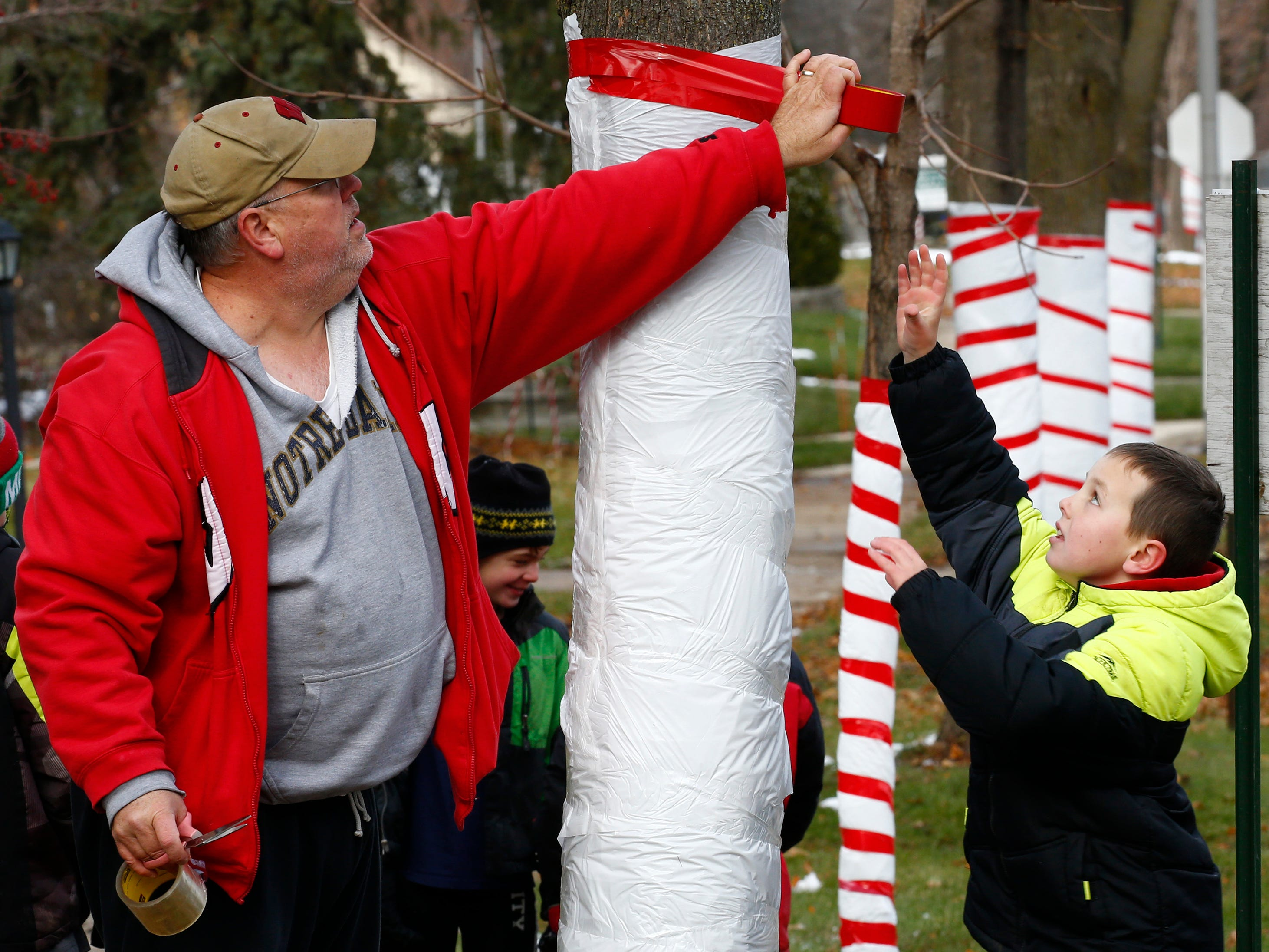 Gregory Ryan stretches to grasp a roll of striping tape to complete another tree in West Allis' Candy Cane Lane. Volunteers from the Midwest Athletes Against Childhood Cancer (MACC) Fund decorated more than 150 trees in the four-block area on Nov. 17 in preparation for Candy Cane Lane's Nov. 23 to Dec. 26 season.