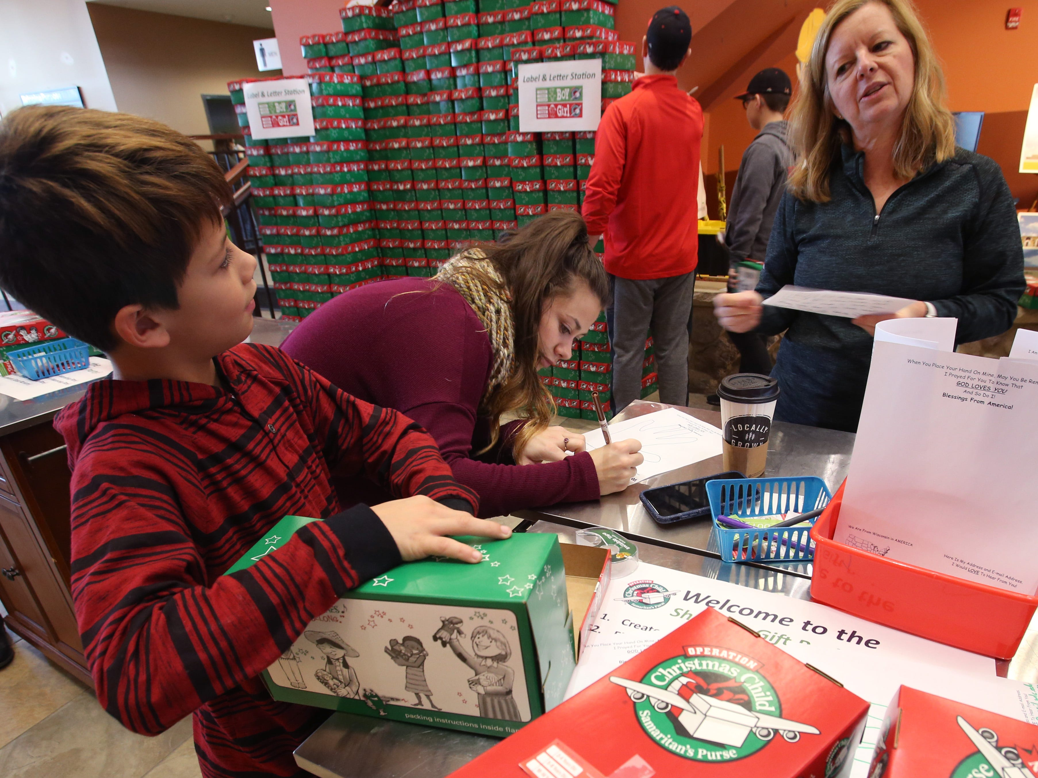 Landon Stevens, Natalie Sternberg and Amy Thorison finish letters and cards to include in shoebox-sized gift boxes to be shipped worldwide through Operation Christmas Child at Mequon's Christ Church on Nov. 17.