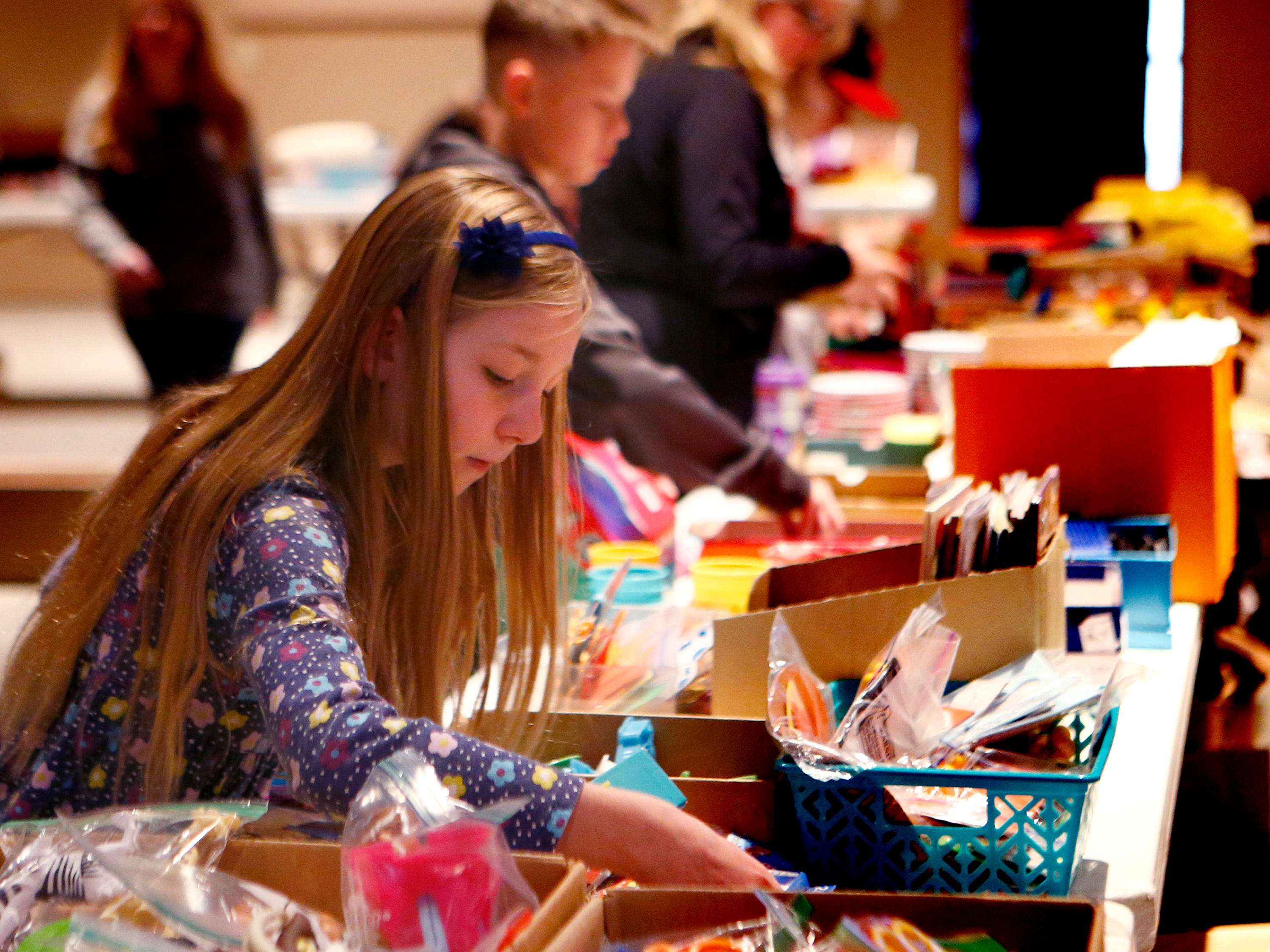 Anna Dietz picks items to fill a shoebox-sized container for the worldwide Operation Christmas Child at Mequon's Christ Church on Nov. 17.