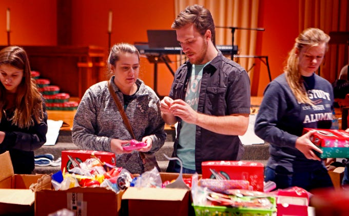 Madison Wirkes and Harrison Krause select school supplies, toys, clothing, personal care items and more to fill a shoebox-sized container for the worldwide Operation Christmas Child at Mequon's Christ Church on Nov. 17.