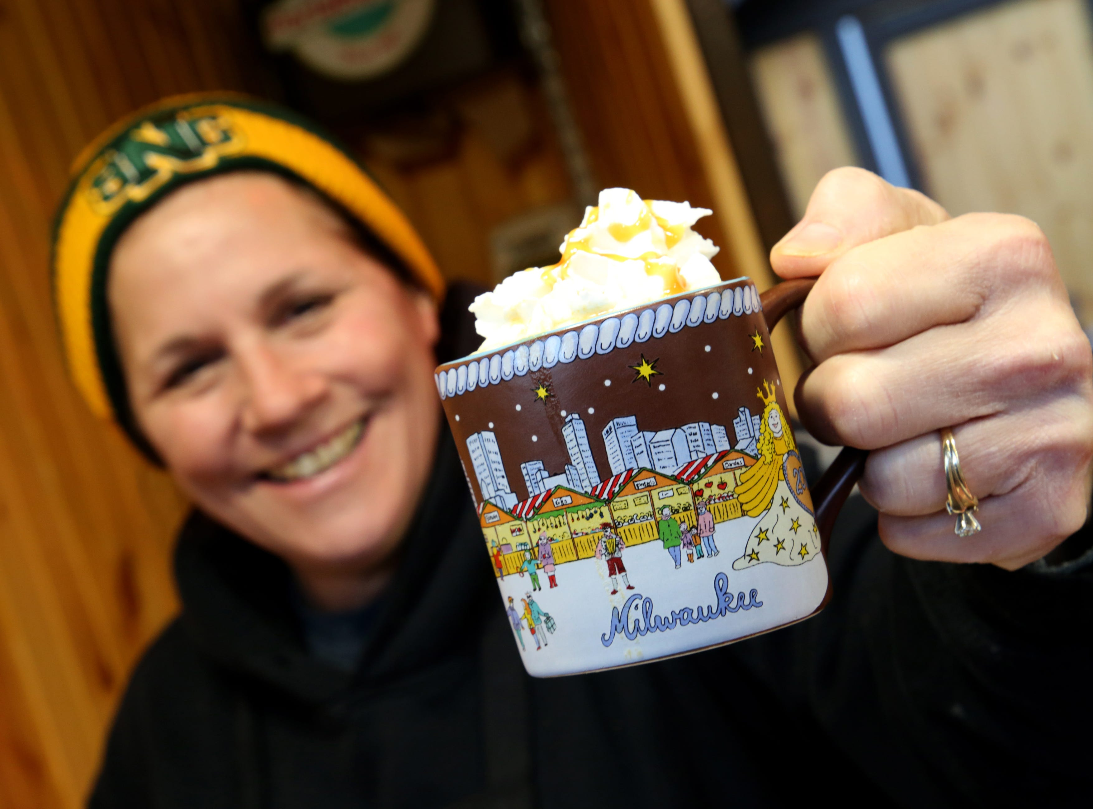 Judy Kozlowski, with the Baked Cheese Haus, holds up a cup of  hot caramel cider.