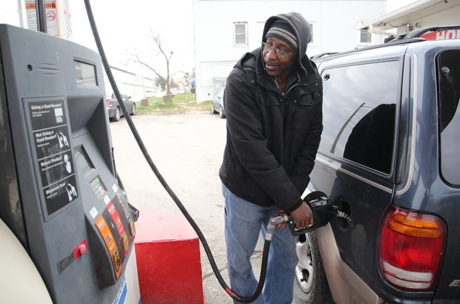 Harold Simms fills up at Hometown Station at 3381 N. 35th St. in Milwaukee on Nov. 19. Gas prices in Milwaukee have fallen sharply this month, and a couple stations in Kenosha were selling a gallon of regular for $1.99 on Friday for cash purchases.