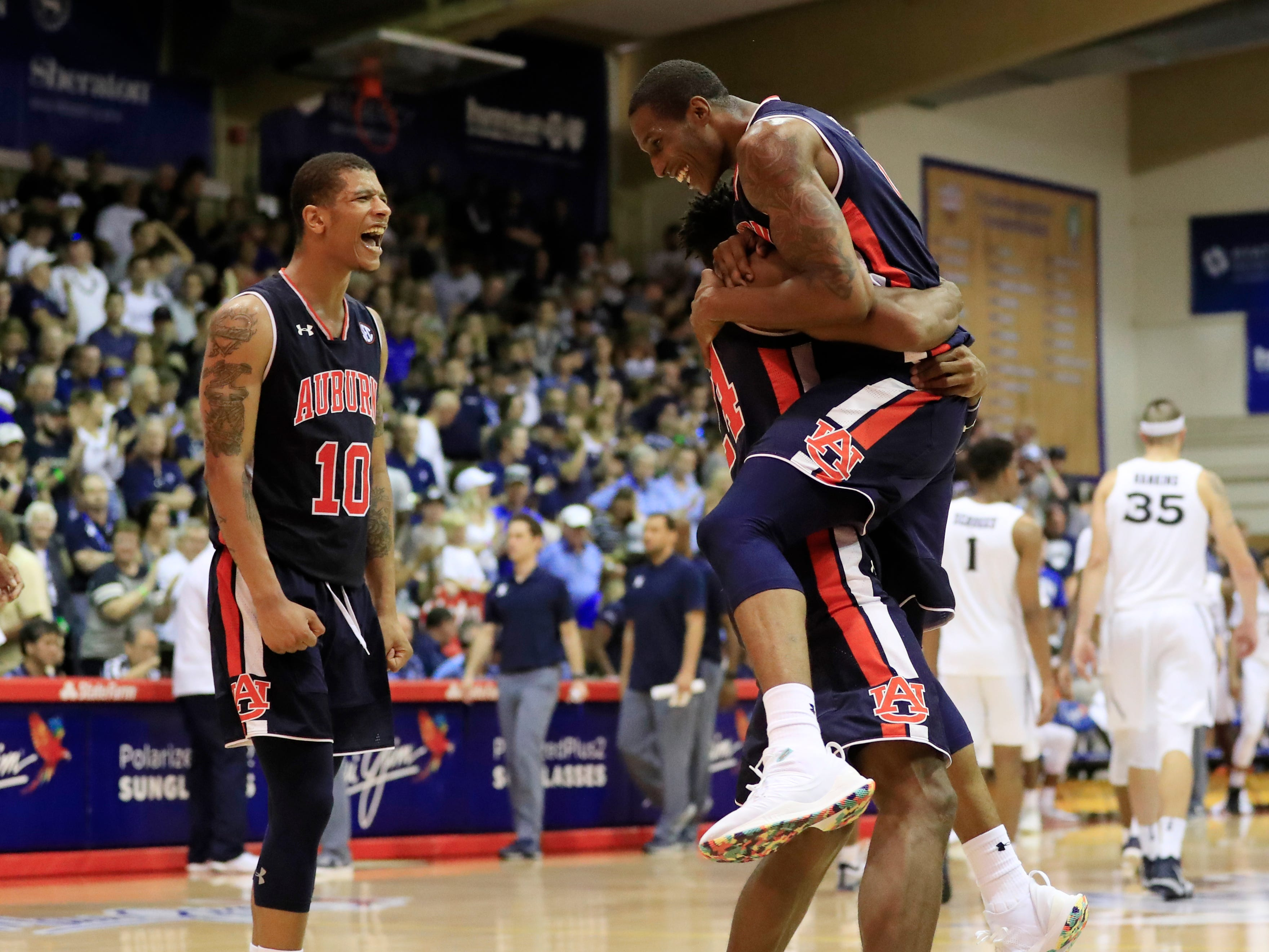 Auburn guard Samir Doughty (10), left, forward Anfernee McLemore (24) and forward Horace Spencer (0) celebrate after defeating Xavier 88-79 in overtime at the Maui Invitational, Monday, Nov. 19, 2018
