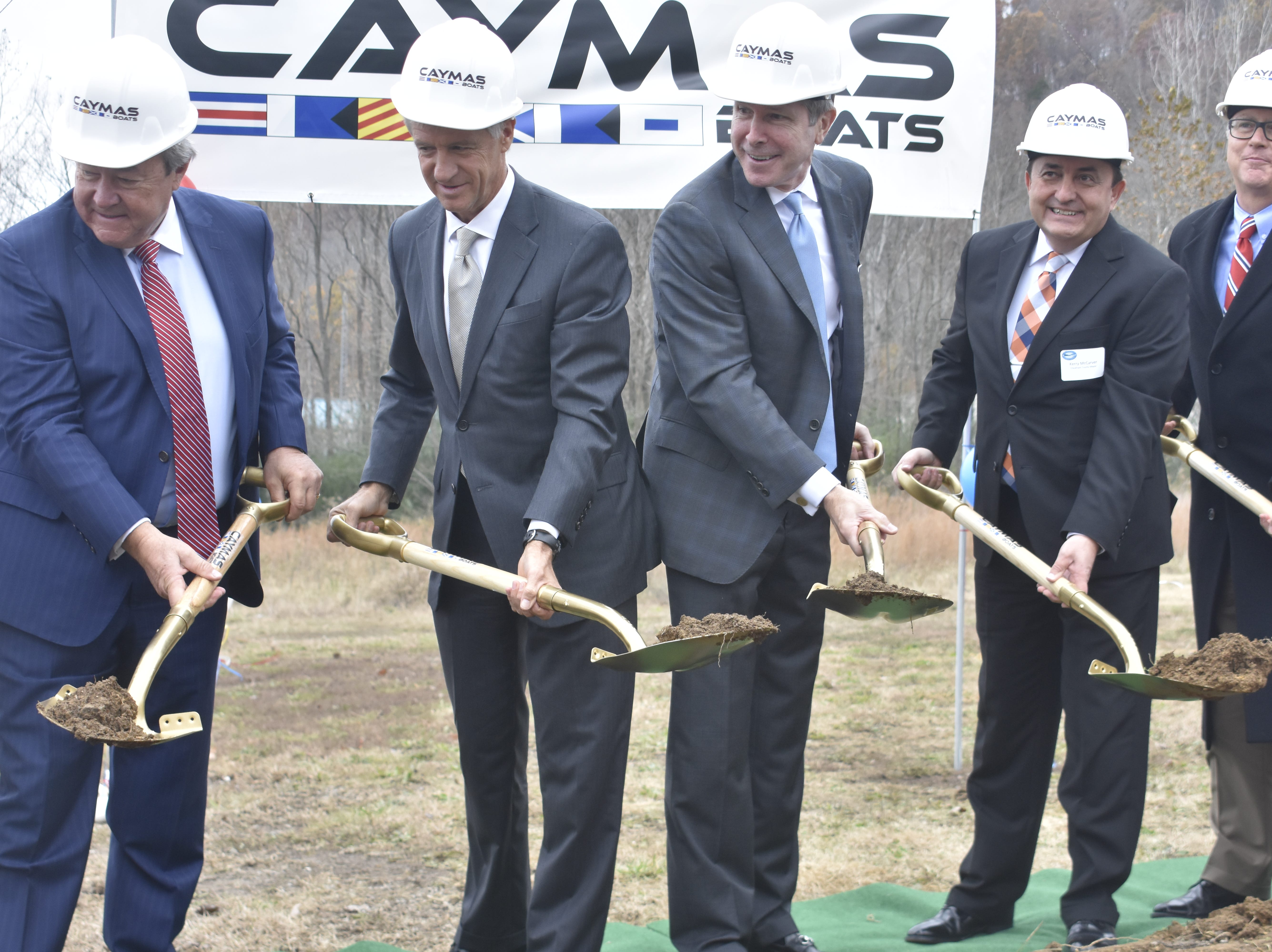 Officials toss dirt at the groundbreaking for Caymas Boats on Monday, Nov. 19 in Ashland City.