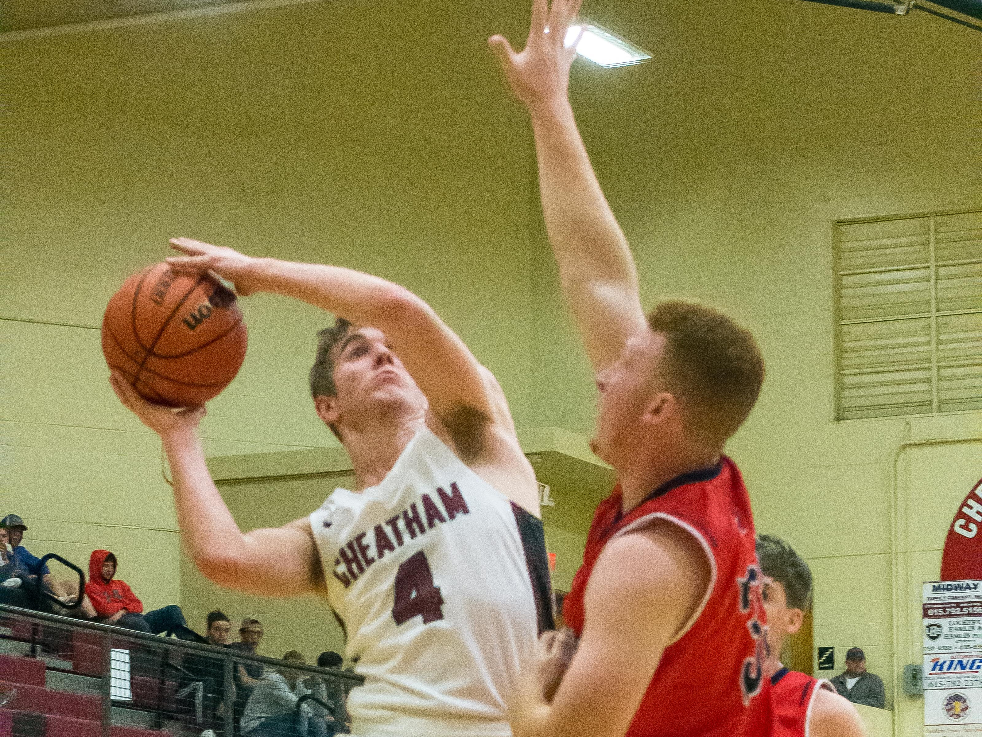 Cheatham County's Charlie Martin manuevers a shot over a Creek Wood defender.