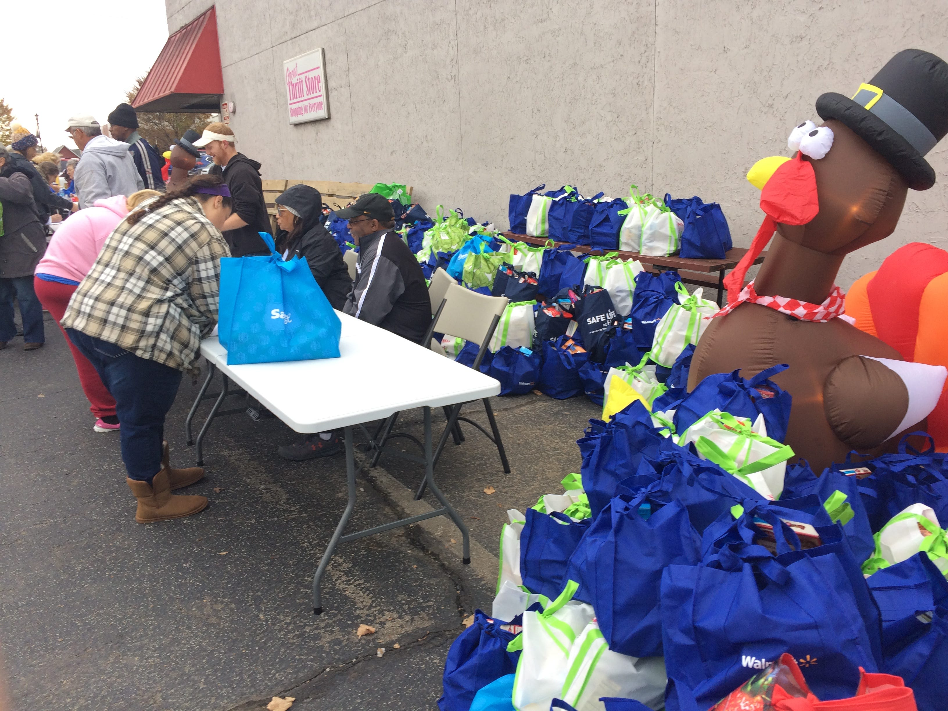 People sign up for a donated turkey and all the fixings, in the bags in back adn surrounding the inflatable turkey, at the Dickson County Help enter on Monday.