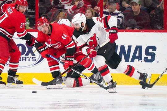 New Jersey Devils right wing Kyle Palmieri (21) skates with the puck past Carolina Hurricanes defenseman Calvin de Haan (44) during the second period at PNC Arena.