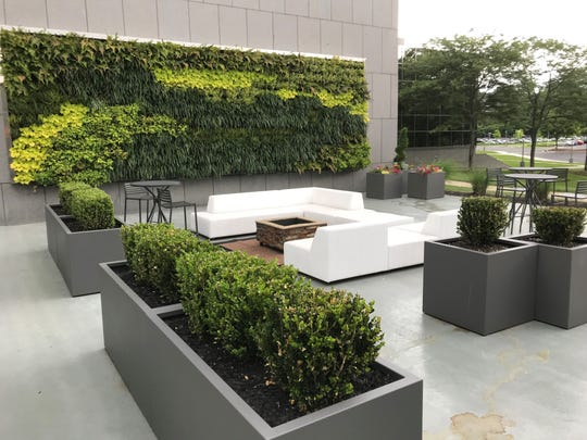 """An outdoor lounge at the 56 at Roseland office building includes a """"green wall"""" lined with plants and fire pits for night-time socializing."""