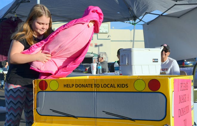 Erika Ernest, 8, deposits her gently used coat in the Coats for Kids donation box.