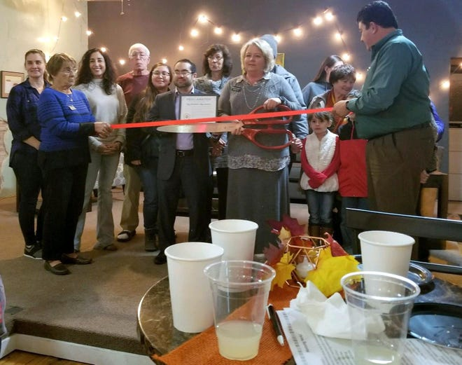 Dawn Starostka, regional director of Big Brothers Big Sisters, cuts the ribbon at the Copper Kettle Coffee Co. to open a new chapter of the nonprofit organization in town.