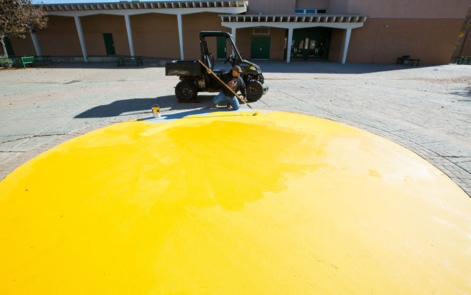 Fernie Herrera, with Las Cruces Public Schools Physical Plant, on Monday Nov. 19, 2018, applies a layer of gold paint on  Mayfield High School's campus where the school's mascot, a Trojan, was vandalized in early November, the week of the school's rivalry football game against Las Cruces High School.