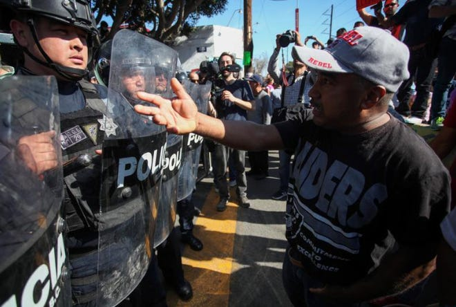 Demonstrators in Tijuana, Mexico, confront police officers Sunday, Nov. 18, 2018, during a protest against the presence of Central American migrants who are waiting to request asylum in the U.S.
