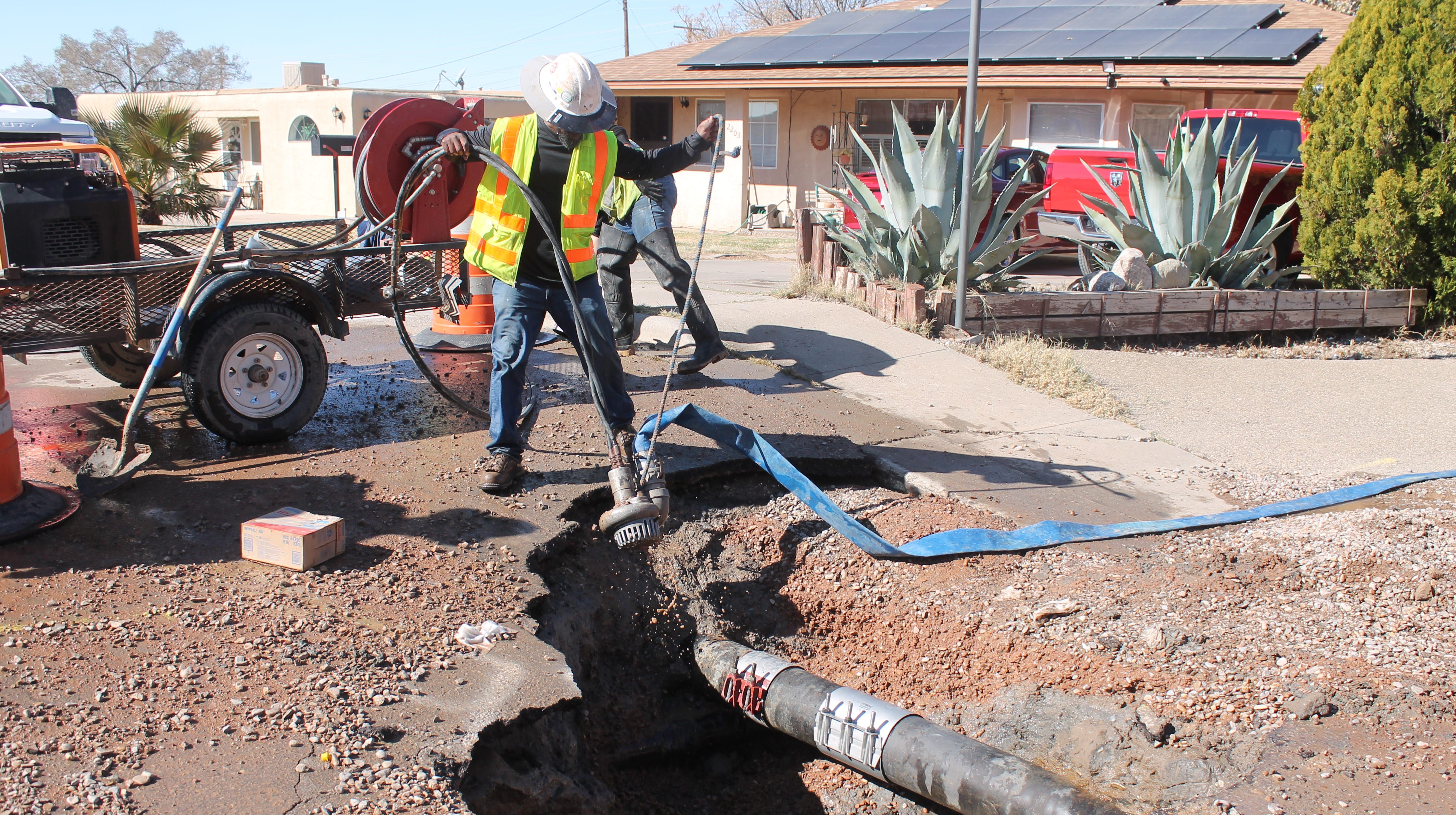 City employee Jamarr Thompson removes a water pump following a repair made to a water main on Bellamah Drive.